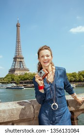 Portrait of smiling modern solo tourist woman in blue jeans overall with retro photo camera near the parapet on the embankment of the river Seine overlooking Eiffel tower in Paris, France.