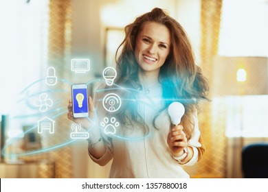 Portrait of smiling modern woman with long brunette hair at modern home showing smart home app on smartphone and smart lamp.