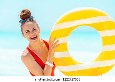 Portrait of smiling modern woman in red swimwear on the seacoast showing yellow inflatable lifebuoy