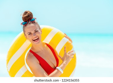 Portrait of smiling modern woman in red beachwear on the seacoast wearing yellow inflatable lifebuoy