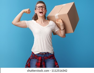 Portrait of smiling modern woman in white shirt with a cardboard box rejoicing isolated on blue