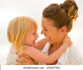 Portrait of smiling mother and baby girl hugging on beach at the evening
