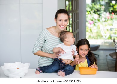 Portrait of smiling mother with children at home