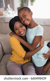Portrait of smiling mother and daughter embracing on sofa at home