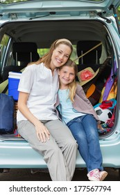 Portrait of a smiling mother and daughter sitting in car trunk while on picnic