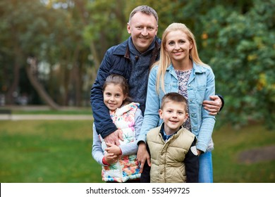 Portrait of a smiling mother and father standing outside with their young son and daughter in a park in the autumn
