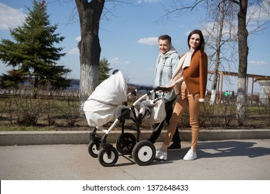 Portrait of a smiling mother and father walking outdoors with baby in baby stroller . Lifestyle Concept.