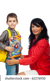 Portrait of smiling mother with her son in first day of school holding books and bag isolate don white background