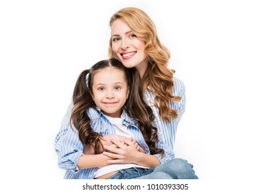 portrait of smiling mother hugging little daughter isolated on white