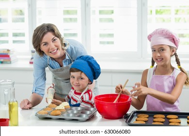 Portrait of smiling mother and kids preparing cookies in kitchen at home