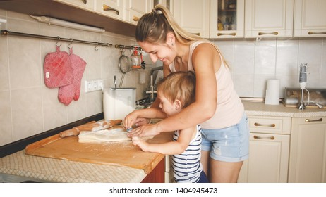 Portrait of smiling mother teaching her 3 years old toddler boy baking and making cookies on kitchen