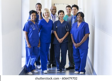 Portrait smiling multi ethnic male female medical team in uniform planning patient treatment in modern hospital