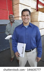 Portrait of smiling multiethnic men with clipboards in front of stacks of wood in warehouse