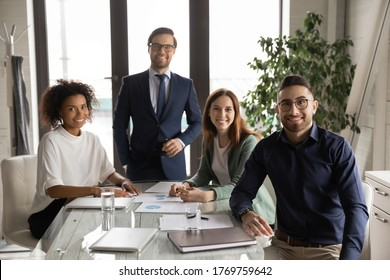 Portrait of smiling multiracial young businesspeople sit at desk in office look at camera poising together, happy multiethnic colleagues show unity and motivation at workplace, teamwork concept