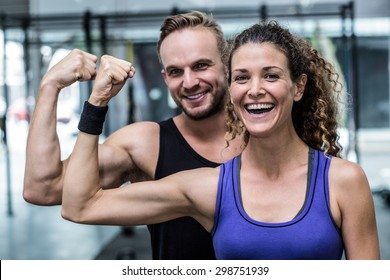 Portrait of a smiling muscular couple flexing biceps