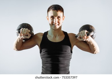 Portrait of a smiling muscular man performing exercises with weights.