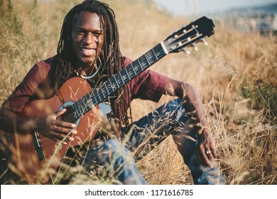 Portrait of smiling  musician African man  wearing dreadlocks playing guitar outdoor
