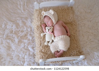 Portrait of a smiling newborn baby girl wearing a bear bonnet. She is cudling a stuffed bear and lying on a tiny bed.