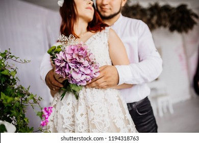 Portrait of smiling newlywed couple at decorated room. Bride and groom picture in  photostudio in white and black colors. Before wedding ceremony. Newlyweds hugs.
