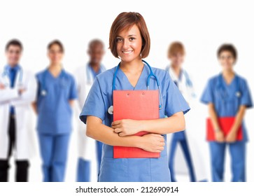 Portrait of a smiling nurse in front of a group of medical workers