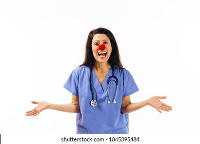 Portrait of a smiling nurse with a red clown nose and arms stretched out, on white background, red nose day