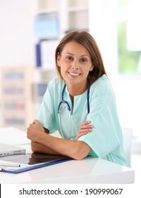 Portrait of smiling nurse studying on laptop computer