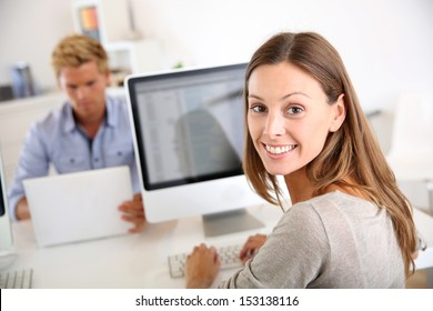 Portrait of smiling office worker in front of desktop