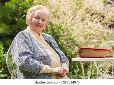 Portrait of smiling old grandmother. Photo on nature background.