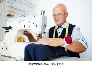 Portrait of smiling old tailor working at sewing machine in traditional atelier studio