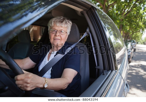 Portrait of smiling old woman driving car