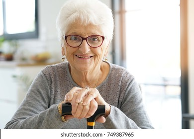 Portrait of smiling old woman holding cane