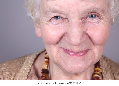 Portrait of smiling old woman. isolated against grey background