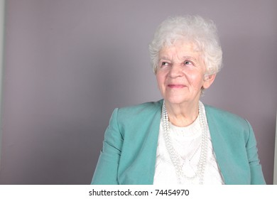 Portrait of smiling old woman isolated against grey background