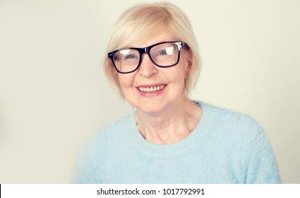 Portrait of a smiling old woman wearing glasses. A beautiful modern grandmother is a pensioner.