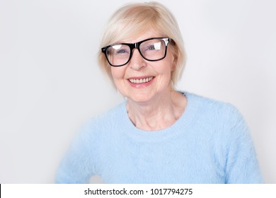 Portrait of a smiling old woman wearing glasses. Beautiful modern grandmother is 70 years old - a pensioner. Senior woman.