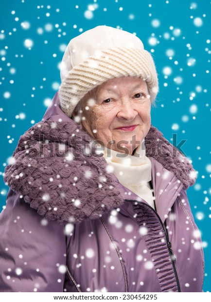Portrait of smiling old woman in winter clothing. Christmas and holidays concept