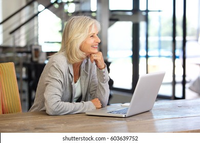 Portrait of smiling older woman working laptop computer indoors