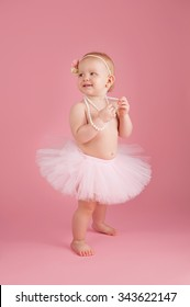 A portrait of a smiling one year old baby girl wearing a pink tutu, string of pearls and flower headband. She is standing on a pink, background with a happy expression on her face.