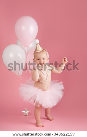 A Portrait Of Smiling One Year Old Baby Girl Wearing Pink Tutu String