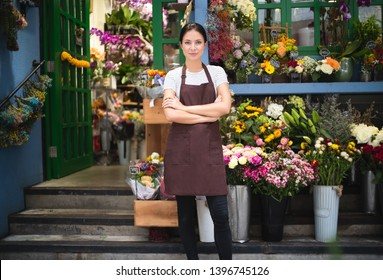 Portrait of smiling owner standing at her flower shop. Young entrepreneur leaning with her arms crossed and smiling confidently at the camera. Startup of small business owner and service mind concept.