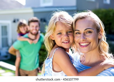 Portrait of smiling parents carrying children in yard