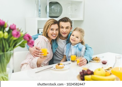 portrait of smiling parents and daughter looking at camera during breakfast at home