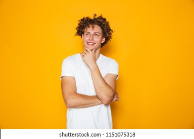 Portrait of a smiling pensive curly haired man looking away isolated over yellow background