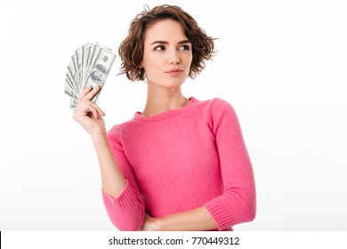 Portrait of a smiling pensive girl holding bunch of money banknotes and looking away isolated over white background
