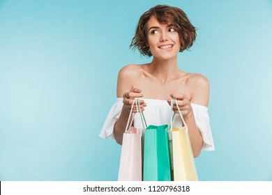 Portrait of a smiling pensive woman holding shopping bags and looking away isolated over blue background