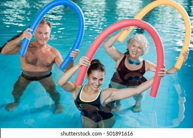Portrait of smiling people doing aqua fitness together in a swimming pool. Group of senior woman and mature man with swim noodles exercising in a swimming pool. Trainer and senior people in aqua gym.