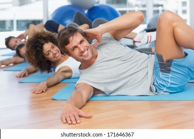 Portrait of smiling people doing pilate exercises in the fitness studio