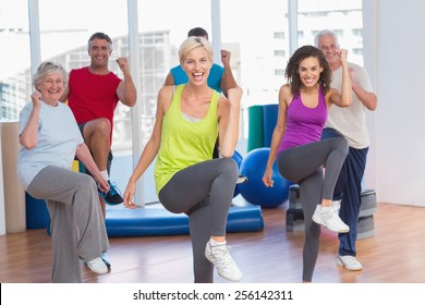 Portrait of smiling people doing power fitness exercise at fitness studio