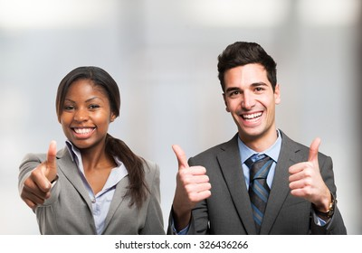 Portrait of smiling people giving thumbs up