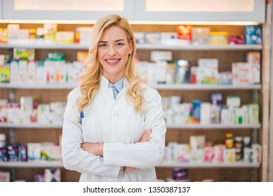 Portrait of a smiling pharmacist with arms crossed at modern pharmacy.